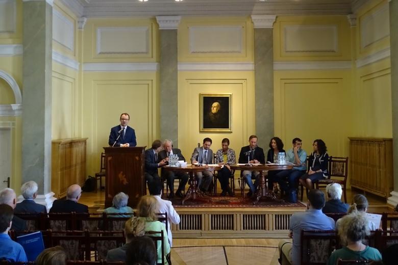 Zdjęcie: paneliści siedzą przy stole, mężczyzna przemawia