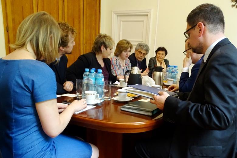 zdjęcie: grupa ludzi siedzi przy owalnym stole, na pierwszym planie kobieta w niebieskiej sukience