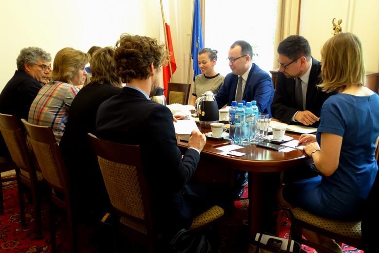 zdjęcie: grupa ludzi siedzi przy owalnym stole