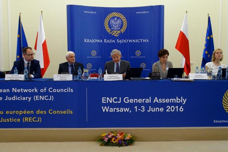 zdjęcie: za granatowym stołem siedzi trzech mężczyzn i dwie kobiety, za nimi widać ściankę z napisem Krajowa Rada Sądownictwa, obok niej stoją polskie i europejskie flagi