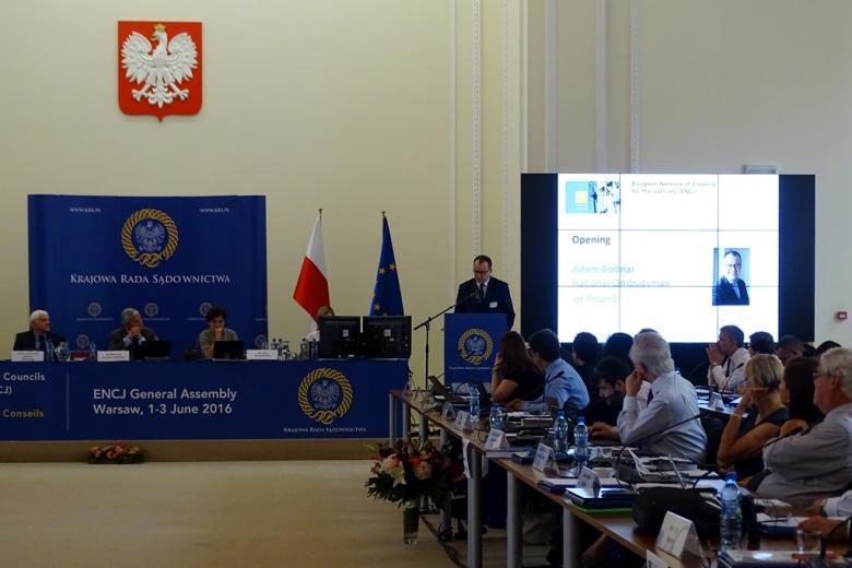 zdjęcie: po lewej stronie jest stół prezydialny, po prawej widać siedzące bokiem osoby