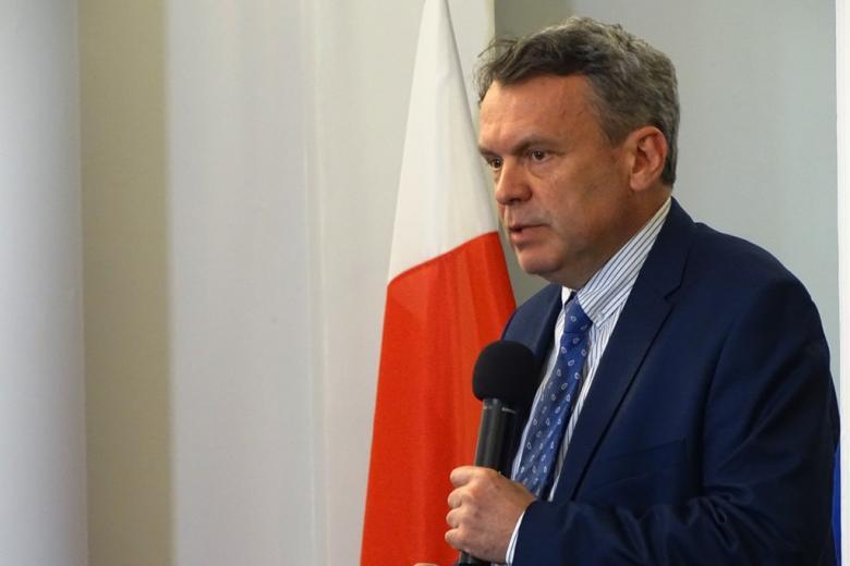 zdjęcie: mężczna w garanatowim garnirurze i błękitnym krawacie, za nim widać fragment polskiej flagi