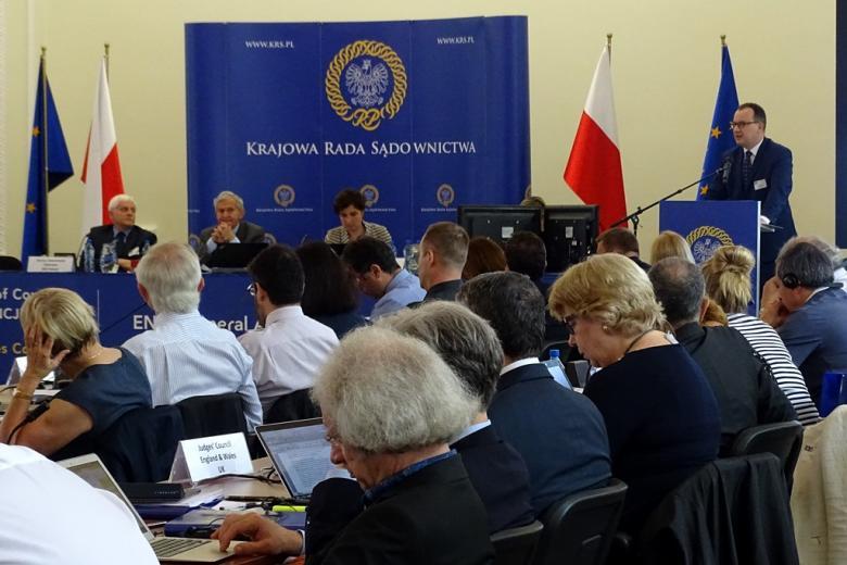 zdjęcie: na pierwszym planie są siedzące tyłem osoby, w tle widać stół prezydialny, po prawej stronie jest mównica, za którą stoi mężczyzna