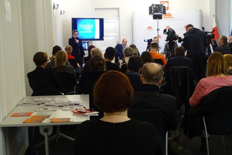 zdjęcie: kilkanaście osób siedzi tyłem , po lewej stronie widać stolik z publikacjami, w oddali kamery
