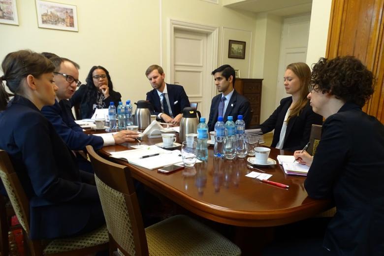 zdjęcie: przy stole siedzi kilka osób, na stole leżą notatki i stoją butelki z wodą mineralną