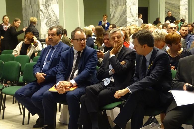 zdjęcie: kilkadziesiąt ocób siedzi na zielonych krzesłach, mężczyźni w pierwszym rzędzie dyskutują