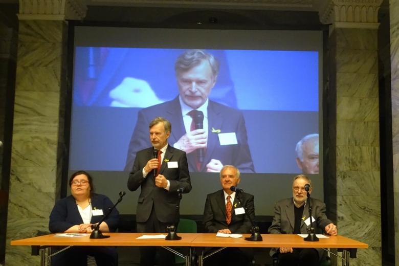 zdjęcie: za stołem siedzą dwaj mężczyźni i jedna kobieta, jeden mężczyzna stoi i mówi do mikrofonu