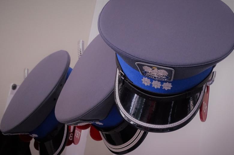 na wieszakach w szatni wiszą trzy policyjne czapki