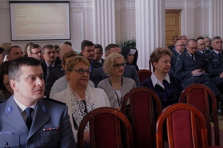 zdjęcie: kilkanaście osób siedzi w sali kolumnowej