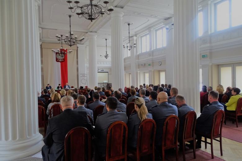 zdjęcie: na sali koumnowej siedzi kilkadziesiąt osób, w tle flaga i godło RP