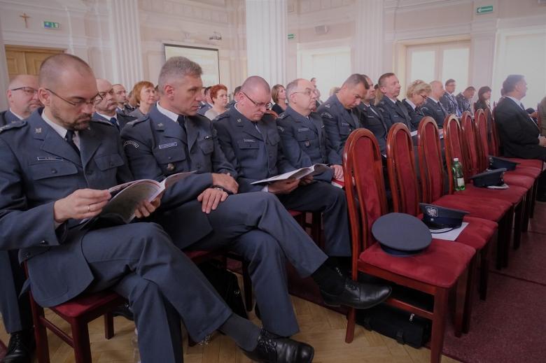 zdjęcie: kilkunastu mężczyzn w granatowych mundurach siedzi i przeglada publikacje