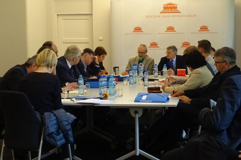 zdjęcie: przy białaych stołach siedzi kilkanaście osób