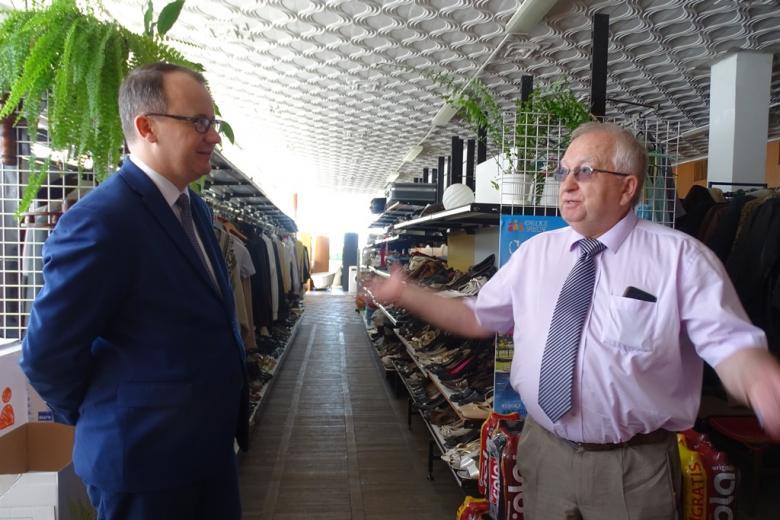 Zdjęcie: dwaj mężczyźni, a w tle - półki z ubraniami