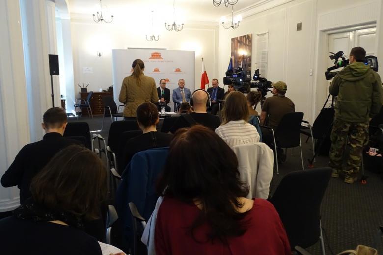 zdjęcie: na pierwszym planie kilku dziennikarzy, w tle siedzi pięć osób