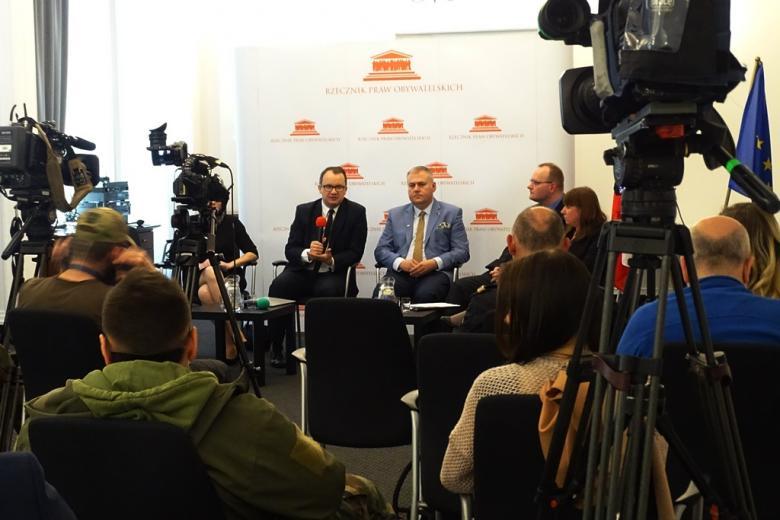 zdjęcie: na pierwszym planie kilka osób siedzi, stoją kamery w tle siedzą dwie osoby