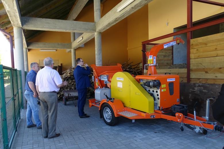 Zdjęcie: żółto-pomarańczowa maszyna i ludzie