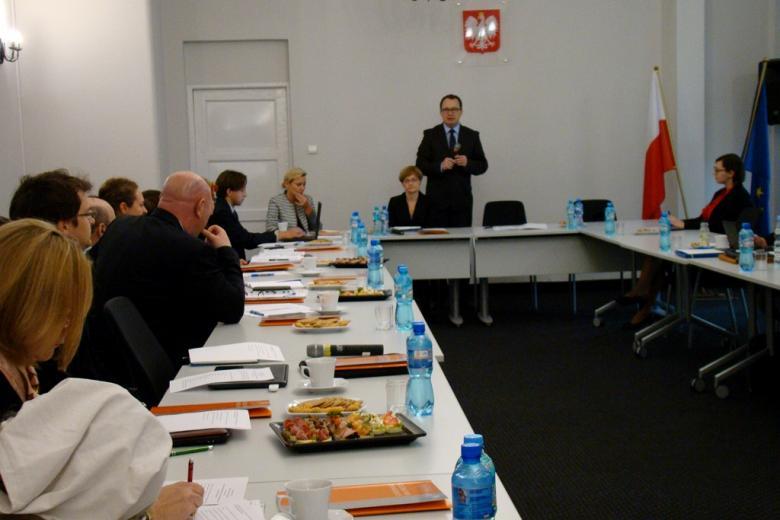Ludzie siedzą przy stole w Biurze RPO, Adam Bodnar stoi