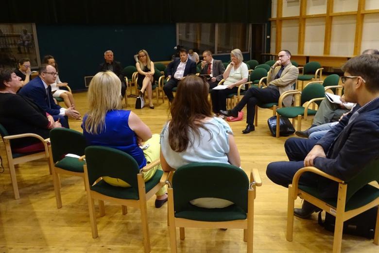 Zdjęcie: ludzie siedzą i rozmawiają w kręgu