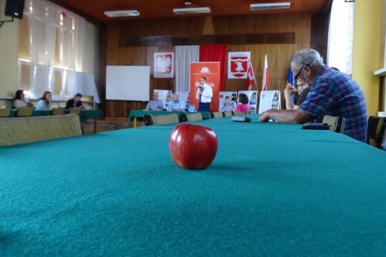 Na pierwszym planie czerwone jabłko; ludzie przy stole