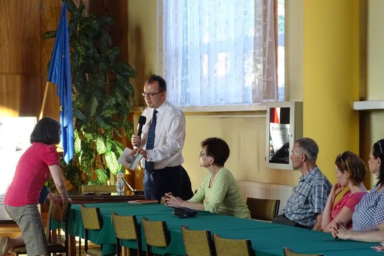 Zdjęcie: mężczyzna w białej koszuli pokazuje zebranym publikację