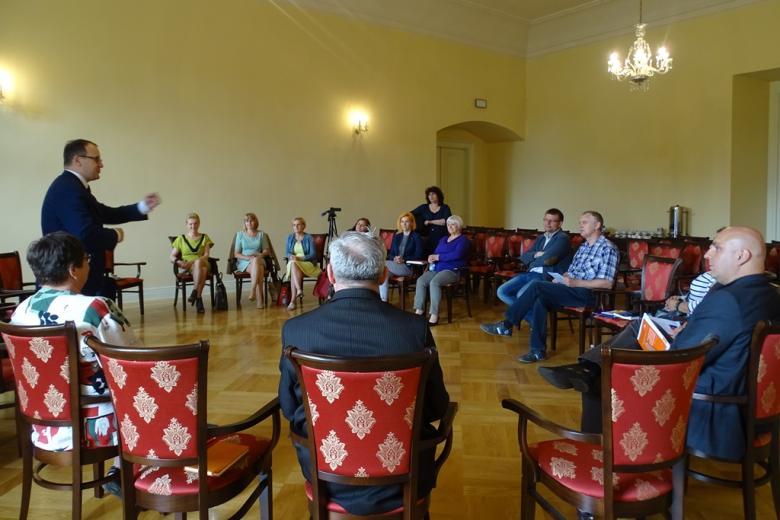 Zdjęcie: grupa ludzi rozmawia w kręgu w zabytkowym wnętrzu, widać czerwono-złote obicia krzeseł