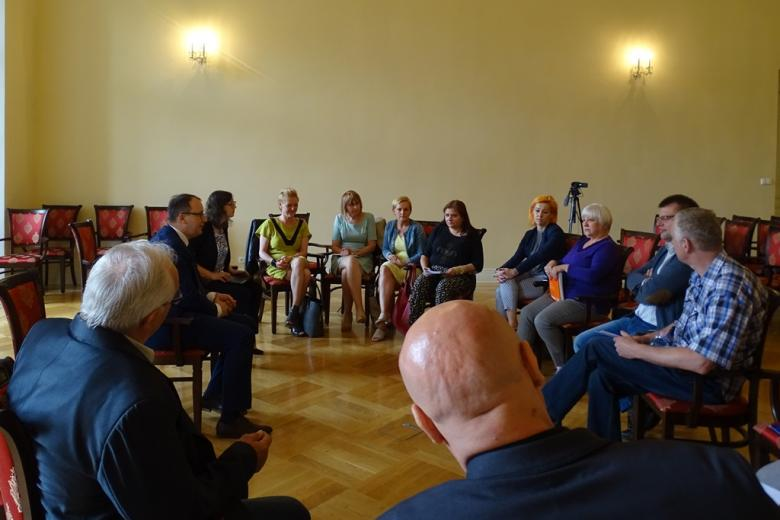 Zdjęcie: grupa ludzi rozmawia w kręgu w zabytkowym wnętrzu