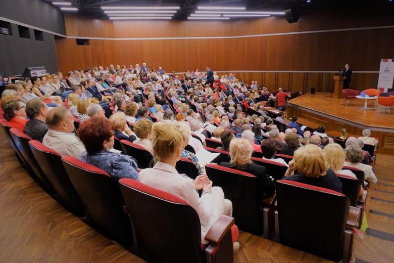 zdjęcie: na scenie przy mównicy stoi mężczyzna przed nim siedzą ludzie
