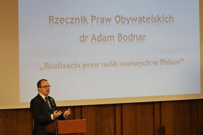 zdjęcie: mężczyzna w garniturze przemawia przy mównicy