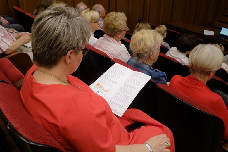 zdjęcie: kilka osób siedzi na auli, jednak z kobiet czyta ulotkę RPO