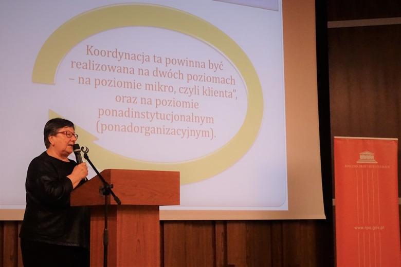 zdjęcie: kobieta stoi przy mównicy, za nią telebim z prezentacją