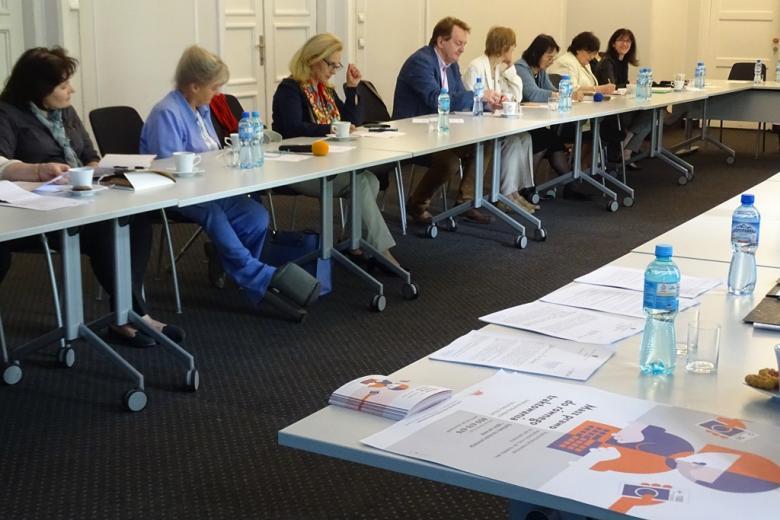zdjęcie: kilka osób siedzi przy białym stole, na pierwszym planie widać leżący na stole plakat dotyczący równego traktowania