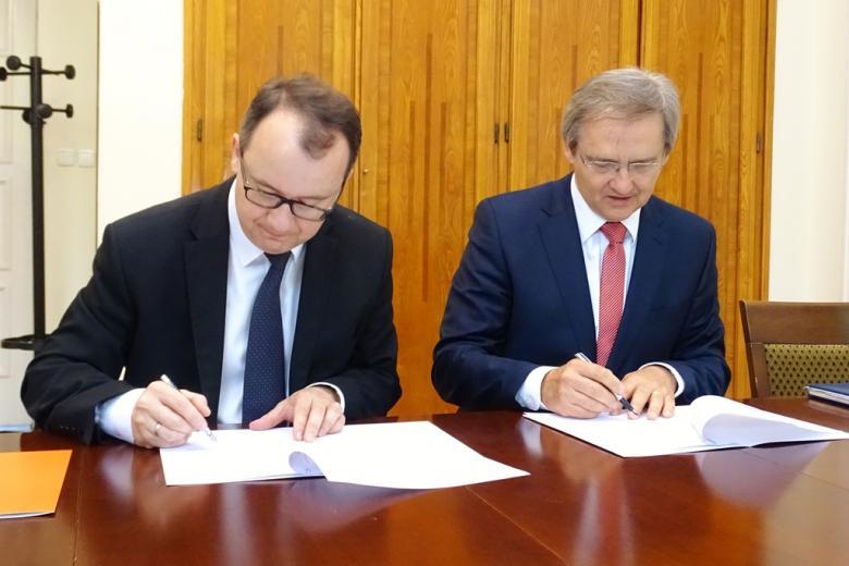 zdjęcie: dwaj mężczyźni siedzą i podpisują dokumenty