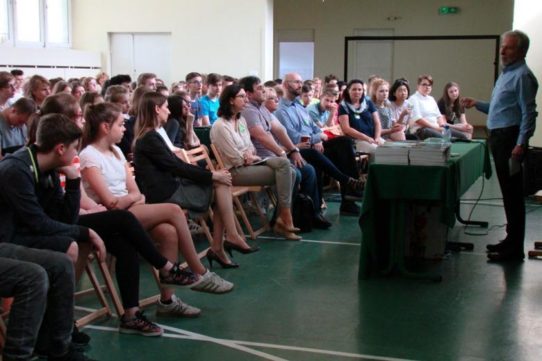 zdjęcie: po prawej stroni stoi mężczyzna w jasnej koszuli, naprzeciw niego siedzi kilkadziesiąt młodych osób