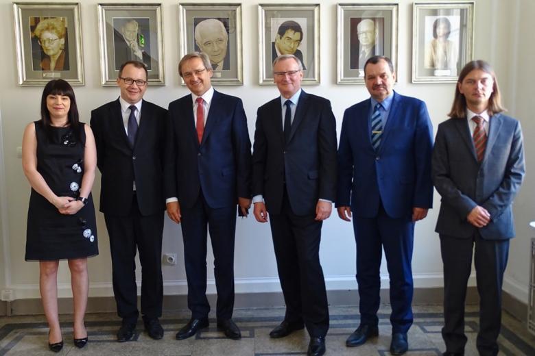 zdjęcie: kobieta i pięciu mężczyzn stoi, w tle portrety