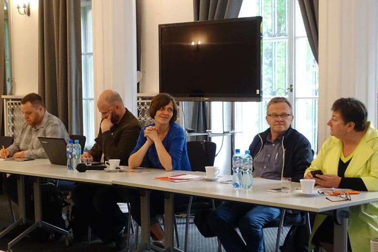 zdjęcie: przy dłubim miałym stole siedzą trzej mężczyźni i dwie kobiety