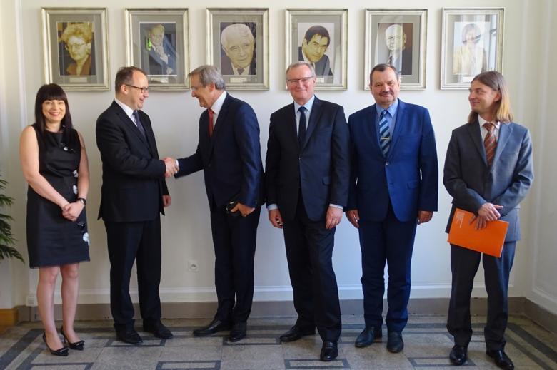 zdjęcie: kobieta i pięciu mężczyzn stoi, dwaj mężczyźni podają sobie dłonie