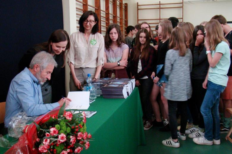 zdjęcie: po lewej stronie stół przy którym siedzi mężczyzna i podpisuje książki, obok niego stoi kobieta, za nią kilkudziesięciu uczniów