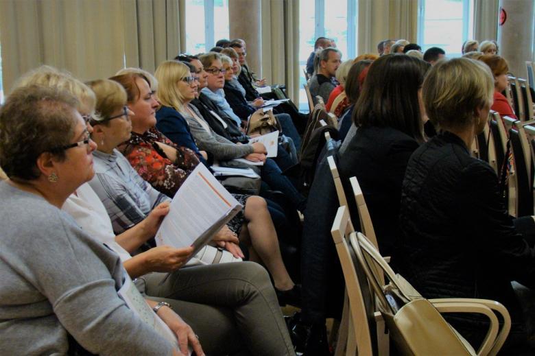 zdjęcie: kilka osó siedzi na sali  i przegląda materiały informacyjne