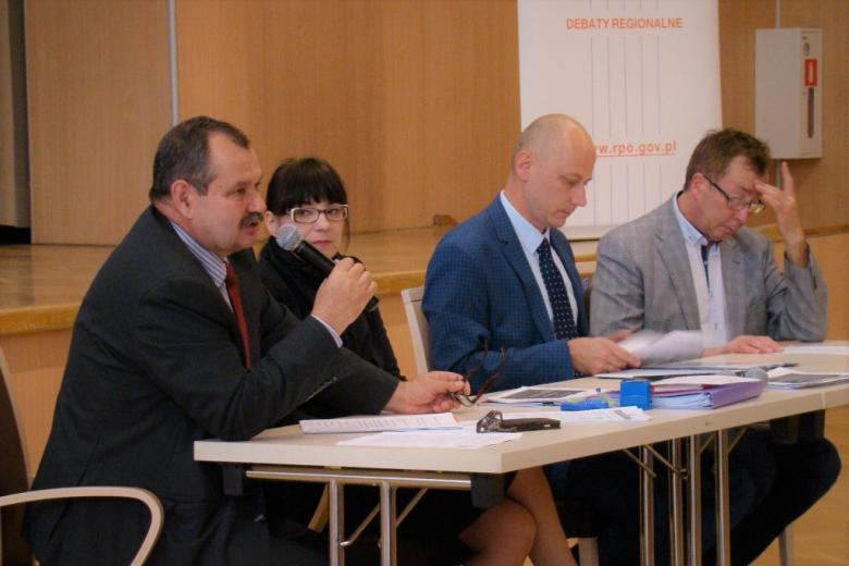 zdjęcie; za stołem siedzą cztery osoby, jedne z mężczyzn mówi do mikrofonu