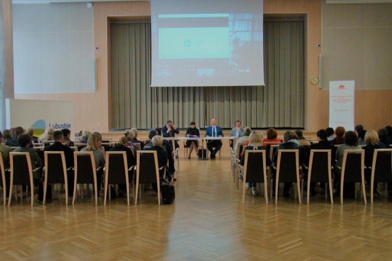 zdjęcie: kilkadziesiąt osób siedzi na sali przed nimi za stołem siedzą cztery osoby