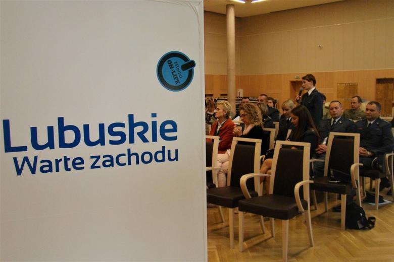 zdjęcie: na pierwszy planie baner z napisem: Lubuskie - warte zachodu. Za nim kilka osób siedzi a pośród nich stoi kobieta w mundurze