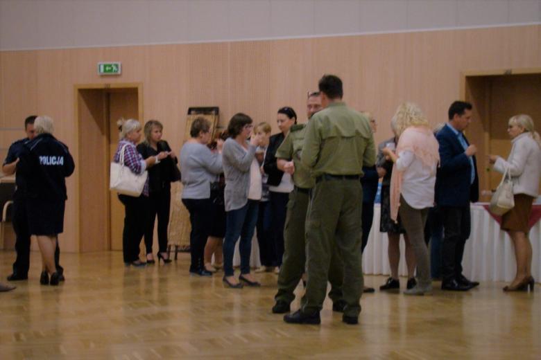 zdjęcie: kilka osób stoi i rozmawia w małych grupkach