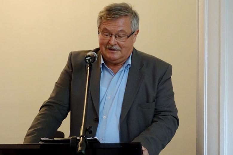 zdjęcie: mężczyzna stoi i przemawia do mikrofonu