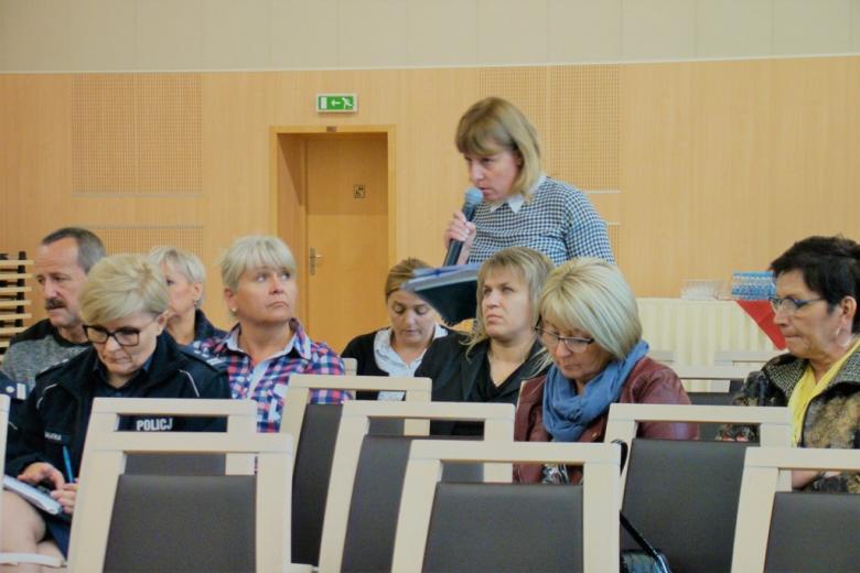 zdjęcie: pośród siedzących osób jedna z osób stoi