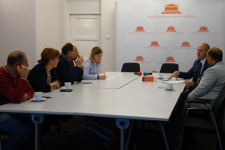 zdjęcie: kilka osób siedzi prz białym stole