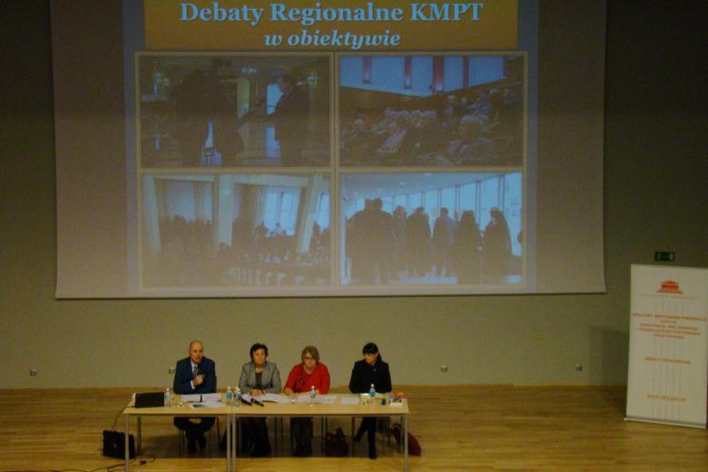 zdjęcie: na scenie przy stole siedzą trzy kobiety i mężczyzna