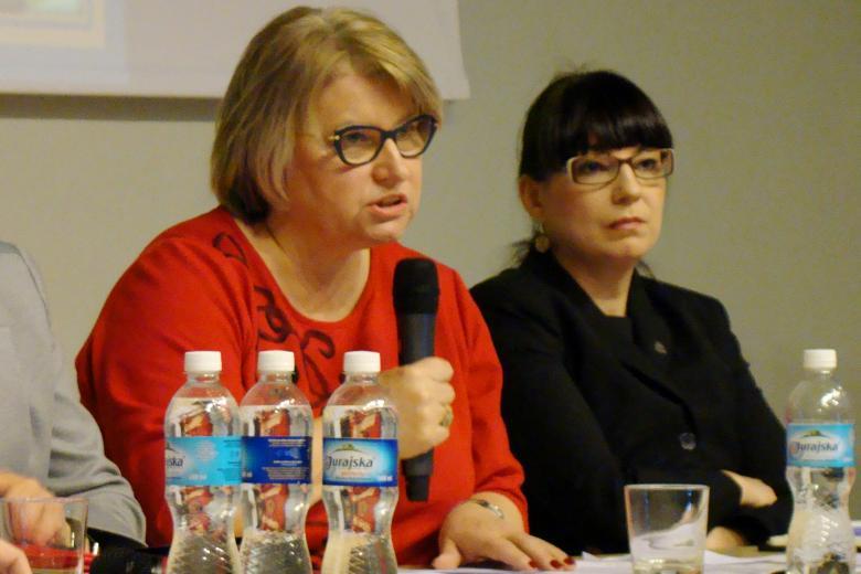 zdjęcie: dwie kobiety siedzą przy stole, jedna z nich mówi do mikrofonu