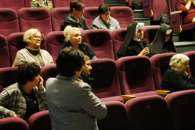 zdjęcie: kilka osób siedzi na sali, jedna z kobiet w habicie mówi do mikrofonu, przed nią stoi kobieta w marynarce