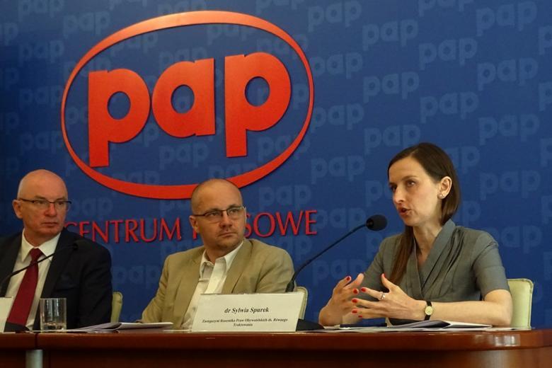 zdjęcie: przy stole siedzi dwóch mężczyn i kobieta, za nimi na granatowym tle czerwony napis: PAP