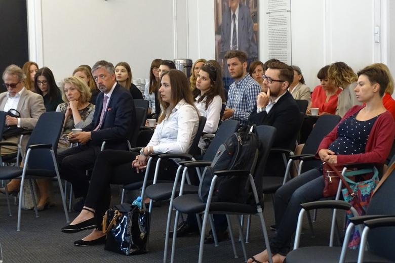 zdjęcie: kilkanaście osób siedzi na krzesłach na sali konferencyjnej